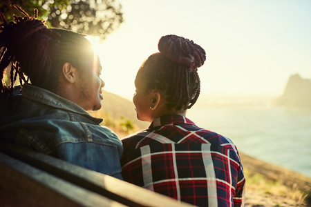 Couple of African descent sitting on a bench looking at each other with appreciation for the beautiful view in front of them and the nature around them during golden hour at sunset in cape town.