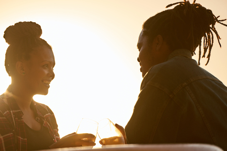 Couple making a toast with some alcoholic beverages, silhouetted by the sunset golden hour behind them, both of african descent, the mixed race woman loves her african mans attention.