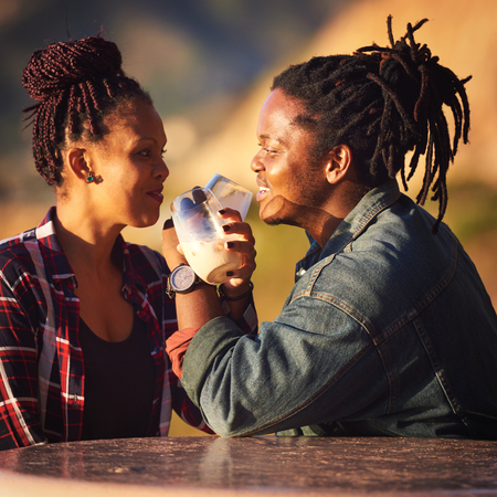 Interracial couple making a toast with interwined arms while looking into each others eyes with cheerful smiles as they enjoy their first outdoor date while seated at a public picnic table in Africa. Reklamní fotografie