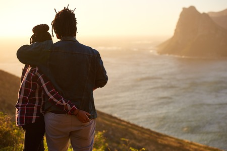 Casually dressed mixed race couple embracing each other while enjoying the awesome view of the ocean and mountains in front of them, taken from behind with the womans hand in the mans back pocket. Reklamní fotografie