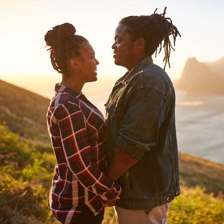 Square image of a mixed race woman and an african man holding hands while facing each other on an outdoor date durind golden hour at sunset with ocean and mountains in the landscape behind them. Reklamní fotografie - 80172539
