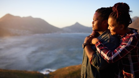 Interracial couple of african descent holding one and other while looking sideways towards the beautiful view of the ocean and mountains in the distance behind them.
