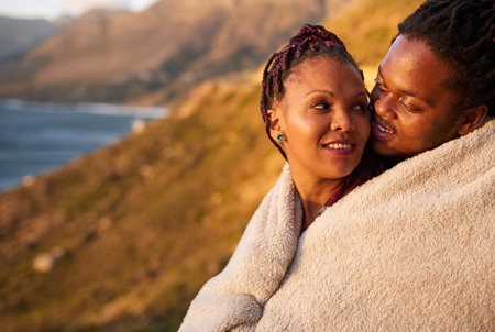 looking for love: Couple keeping warm under a blanket outdoors, with a stunning view of mountains and the ocean behind them, they enjoy an inimate moment with each other by showing their affection for one and other.