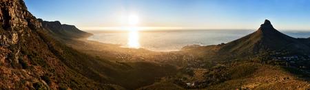 Breed landschapsbeeld met hoge resolutie dat in Kaapstad, Zuid-Afrika tijdens gouden uur vlak vóór zonsondergang, met een mening van de oceaan, de stad en de omringende bergen wordt genomen.