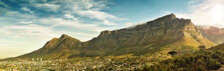 detailed image: Breathtaking landscape panorama of table mountain, in cape town, south africa, with dramatic clouds and warm sunlight casting a shadow from the mountain over the city. Stock Photo