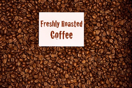Overhead image of freshly roasted coffee beans with a freshly roasted coffee sign on top of the beans on a white sheet of cardboard.