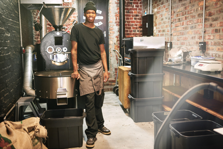 African worker standing in a coffee roasting room next to a coffee bean roaster in an industrial setting amongst all the other stored coffee beans and stored machinery. Reklamní fotografie