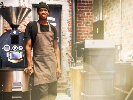 African male employee smiling at camera while standing next to a coffee roasting machine amongst some other machinery to do with the making of coffee.
