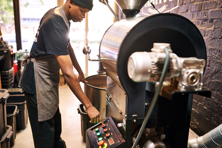 African man pushing red button on an industrial coffee machine, with large windows in the background allowing ample light into the space from behind the man. Reklamní fotografie - 96224531