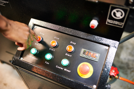 Black hand busy pushing red button on an industrial looking panel of switches for a coffee roasting machine