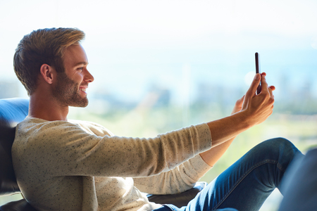 Profile image of a handsome young caucasian man smiling while taking a selfie with his mobile phone, with a gorgeous view of the cityscape in the distance behind him through the large glass window.