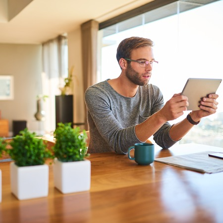 Square image of modern caucasian man sitting at the stunning dining table in his modern home with beautiful large glass windows, while reading his electronic tablet with his morning coffee.