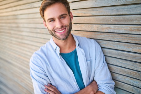 Tightly cropped image of handsome young male in his mid 20s smiling at camera with his teeth showing and his arms crossed while leaning against beautiful wooden cladding outdoors.