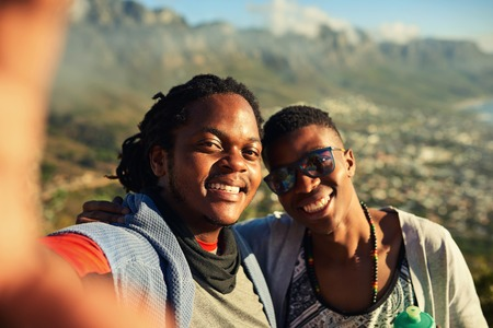 Two happy male african friends take a selfie together while hiking outdoors with gorgeous mountains in the background and true emotion in their smiles. Stok Fotoğraf