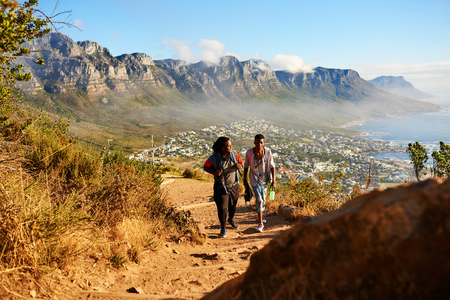 Two black male friends hiking a mountainous trail with a stunning scene of mountains, ocean and city scape behind them, as they ascend the mountain, continuing on their path.
