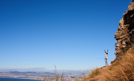 African man standing on a mountain outdoors with his arms and hands wide open facing a magnificent view and clear blue sky over an amazing city scape.