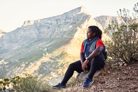 African hiker taking a break sitting next to the hiking trail on a mountainous trail to take in the amazing views of all the mountains around him that surround the amazing city scape. Reklamní fotografie