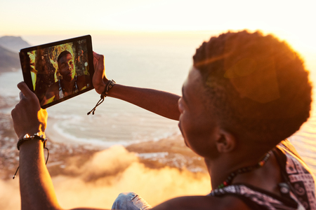 Young stylish black teenager busy using a tablet to take a selfie of himself on the top of a mountain trail while hiking on mountainous terrain on a warm sunny day with clouds in the view below him.
