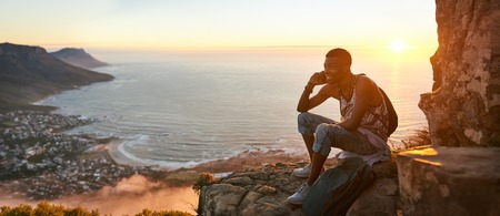 Panoramic image of a young black man sitting on the top of a mountain talking on a mobile phone during an amazing sunset, with a beautiful view of the ocean and cityscape in the background. Reklamní fotografie