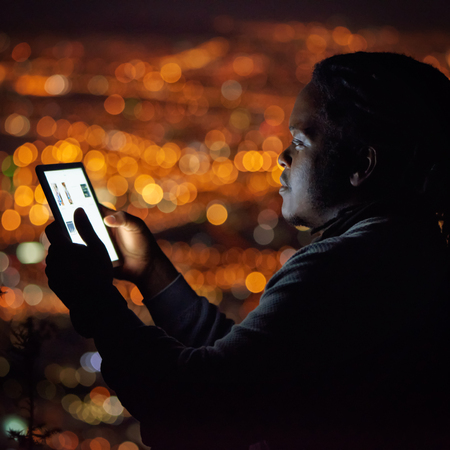 Square image of an African man busy using an electronic tablet with a beautiful bokeh of city lights in the background behind him, and his face illuminated by the light emanating from the screen.