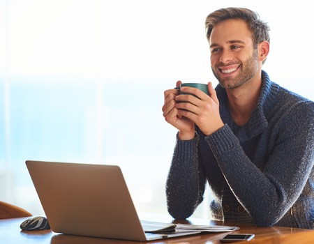 Handsome young caucasian man, happily smiling while holding his coffee mug for warmth in the morning, as he prepares for work with a positive attitude. Reklamní fotografie