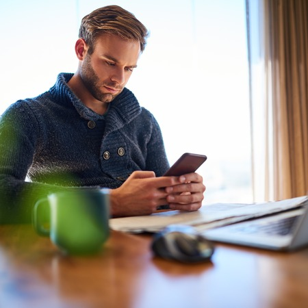 square image of handsome young white man busy texting on his phone while seated at his desk at work, procrastinating instead of working. Reklamní fotografie