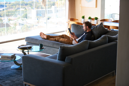 wide image of good looking caucasian man lying on a large couch in a modern living space in a gorgeous house and the latest technologies.