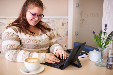Plus size caucsian woman happily smiling while working on her tablet and keyboard in a bright cafe with a morning cup of coffee to be more productive. Reklamní fotografie