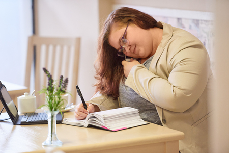 Plus size woman busy multitasking in a coffee shop, talking in on her mobile phone while taking notes in her diary, while looking at her calendar to check her dates and availability.