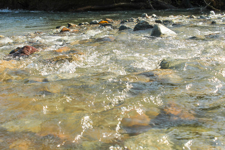 Stream flowing fast over rocks Stock Photo