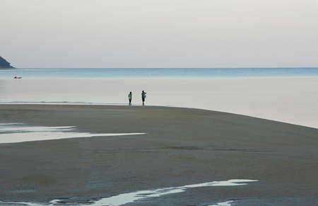 Tourists enjoy beach travel on vacation., Happy tourist silhouette enjoying morning beach walk.
