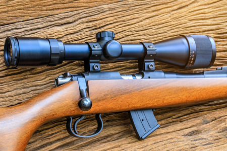 The riflescopes  on old wooden  background . Foto de archivo