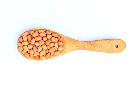 Peanut in the wooden spoon isolated on white background Фото со стока