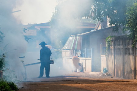 The man are spraying fumes in the village to prevent dengue fever. Reklamní fotografie