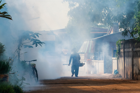 The man are spraying fumes in the village to prevent dengue fever. Stock Photo