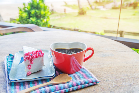 Coffee  in the red cup and cake  for breakfast in the garden on the beach.