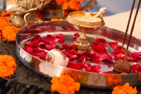 Hindu puja, offering to gods. Incense, rose petals, marigold flowers, goddess Saraswati statue. Traditional, indian, altar, religion, holiday, Navratri, still life.