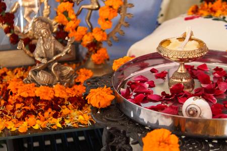 Hindu puja. Incense, rose petals, marigold flowers, goddess Saraswati and god Shiva figures. Traditional, indian, altar, religion, holiday, Navratri, still life.