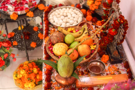 Hindu puja, offering to gods. Incense, fruits, sweets, rose petals, marigold flowers, statues of the gods. Traditional, indian, altar, religion, holiday, Navratri, still life. Banco de Imagens