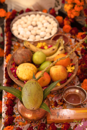 Hindu puja, offering to gods. Incense, fruits, coconut, sweets, rose petals, marigold flowers, statues of the gods. Traditional, indian, altar, religion, holiday, Navratri, still life.