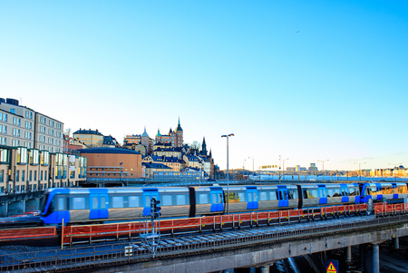 Stockholm, Sweden : view of Sodermalm city district area on a sunny evening. Historical buildings, reflections in the windows. The train goes over the bridge.