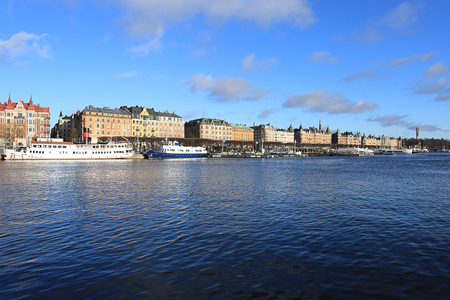 Stockholm, Sweden : view of the embankment with yachts and historical buildings on a sunny day. Sky reflection in a water.