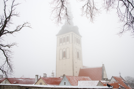 Famous view of St. Nicholas or Niguliste church on a foggy winter day in Tallinn old town. Beautiful red tiled rooftops under the snow. Landmark of Estonia. Winter fairy tale. Stock fotó