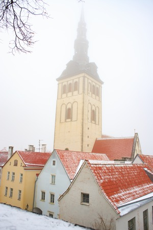 Famous view of St. Nicholas or Niguliste church among red tiled rooftops on a foggy winter day in Tallinn old town. Landmark of Estonia. Winter fairy tale.