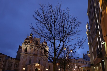 Beautiful baroque church of St. Casimir in Vilnius, Lithuania at blue hour. Historical buildings, city lights, tree., evening, dusk.