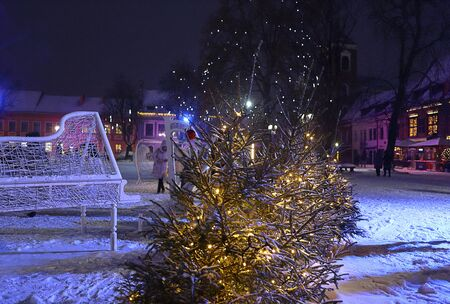 Christmas tree, holiday decoration, illumination and falling snow. Enchanting evening, winter wonderland. Town Hall square in Kaunas old town, Lithuania. Postcard, greeting card, New Year vacation.