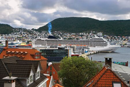 Picturesque view of Bergen. Mountains, clouds, cityscape, wooden houses with tiled roofs, cruise ships. Hordaland, Norway. Stock fotó