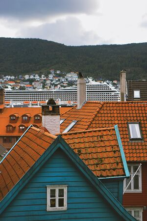 Picturesque view of Bergen. Mountains, clouds, cityscape, wooden houses with tiled roofs, cruise ship. Hordaland, Norway. Stock fotó