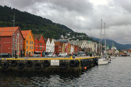 Famous view of Bergen city center and historic quarter Bryggen. Fjord, mountains, yachts, traditional colorful wooden houses. Norway, Hordaland. Scandinavian landmark.