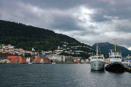Famous view of Bergen harbor and historic quarter Bryggen. Fjord, mountains, ships, traditional colorful wooden houses. Norway, Hordaland. Scandinavian landmark. Stock fotó
